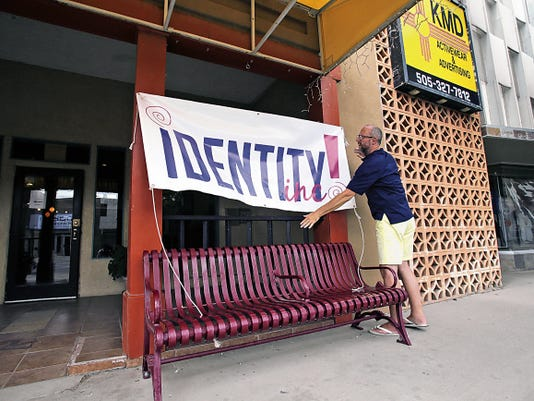 Donald Stage, treasurer and board member for Identity Inc., hangs a sign in front of the organization's community center Thursday in downtown Farmington. Identity Inc. could receive more than 4,000 in Community Development Block Grant funds.