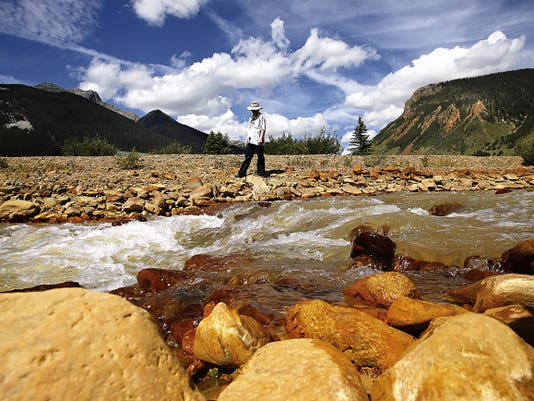 Melanie Bergolc, of Silverton, Colo., walks on Aug. 10 along the banks of Cement Creek in Silverton, days after the Gold King Mine spill released toxic wastewater into the Animas River.