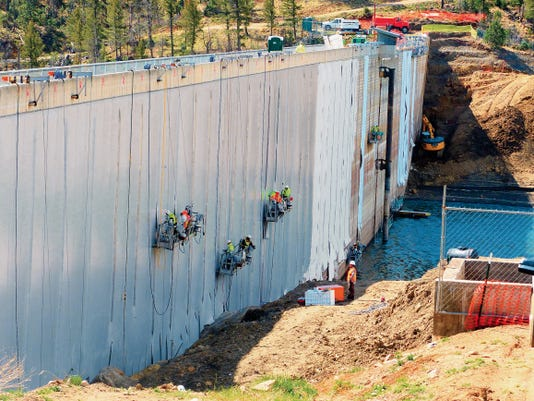 Crews from CARPI USA hang from the top of Grindstone Dam as they apply the synthetic material and adhesive to the face of the dam to eliminate leakage. Village officials hope the work is completed in time to capture some of the snowpack run-off in the Ruidoso River to refill the reservoir.
