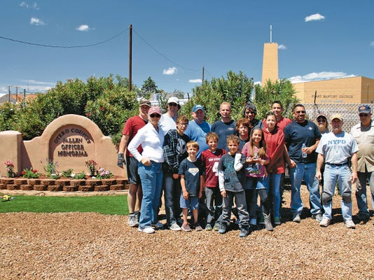 Volunteers posed for a photo next to the Otero County Fallen Officer Memorial at Tenth Street and Michigan Avenue after laying gravel and artificial grass, planting flowers and making other improvements to the memorial's grounds Saturday. Members of the New Mexico State Police, Alamogordo Police Department and 12th Judicial District Court, along with their families, assisted with the effort to improve the approximately 8-year-old memorial for Otero County law enforcement who gave their lives in the line of duty. The family of one of the officers honored at the memorial also volunteered their time. The Home Depot, Lowes Home Improvement and the La Luz-based company Jobe donated the materials for the project.