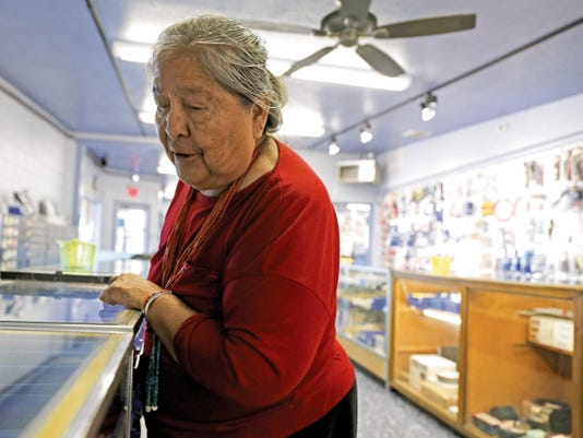 Jean Dejolie, of Navajo Mountain, Utah, looks at jewelry in a display case Thursday at Monsterslayer Inc. on U.S. Highway 64 in Kirtland.