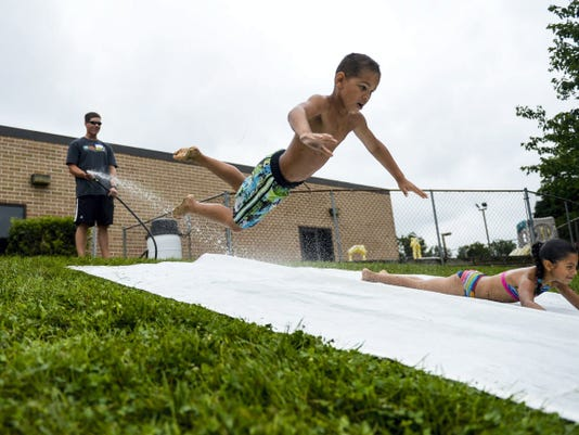"""Kaden Schultz-Tillison, 7, goes airborne as he races Julianiliz Vazquez, 7, at the Lebanon Valley Family YMCA. About 175 kids from the seven summer camp locations run by the Lebanon Valley YMCA, along with the help of 15 volunteers from the Hershey Co., participated in """"water Olympics"""" at the YMCA on Wednesday"""