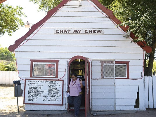 A customer leaves with her burger on Friday at the Chat and Chew restaurant in Shiprock. The burger joint has not changed much during its 65 years in existence.