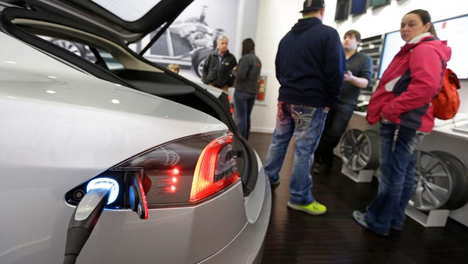 Customers check out a Tesla electric car at a Tesla showroom inside the Kenwood Towne Centre in Cincinnati.