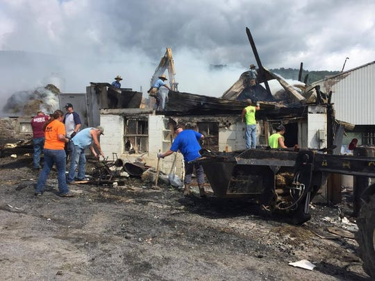 Community members help clean up debris from a large barn in the 2400 block of Back Road was destroyed during a fire in the early morning hours of June 25. The barn was a part of Bruce D. Gamble and Sons Feed and Supply.