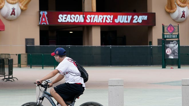 A Los Angeles Angels fan rides a bike past the entrance of Angels Stadium on Wednesday, July 1, 2020, in Anaheim, Calif. The Angels and other Major League Baseball teams will report to their respective facilities for training this week, amid the coronavirus pandemic.