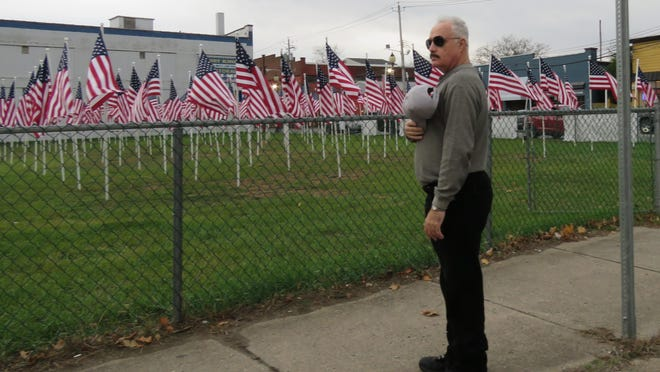 """Guy Spradling joins in a salute of 140 local heroes represented in the Port Jervis Rotary-hosted Flag of Fields, including a flag sponsored by Spradling for Homer """"Slim"""" Spradling, Army Master Sergeant WWII."""