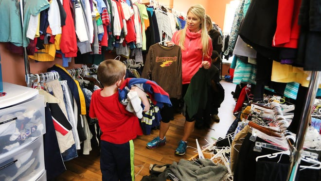 Rachel Henry helps Payton Bray, a kindergartner at Oyler Community Learning Center in Lower Price Hill, with some clothing choices from the Madhatter's Closet.