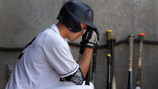 Bay Port's Zach Abfall sits alone in the dugout in the closing moments of a 1-0 loss against Oconomowoc in a WIAA Division 1 state baseball quarterfinal game Tuesday at Neuroscience Group Field at Fox Cities Stadium in Grand Chute.