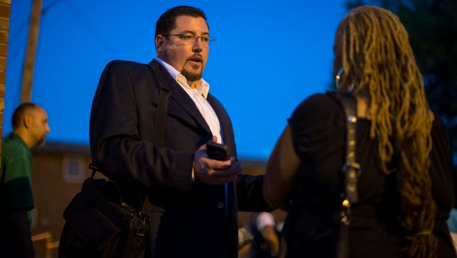Ferguson Mayor James Knowles speaks with resident Juanita Stone after a town hall meeting with local government officials and residents on Tuesday, at Our Lady of Guadalupe in Ferguson, Mo.