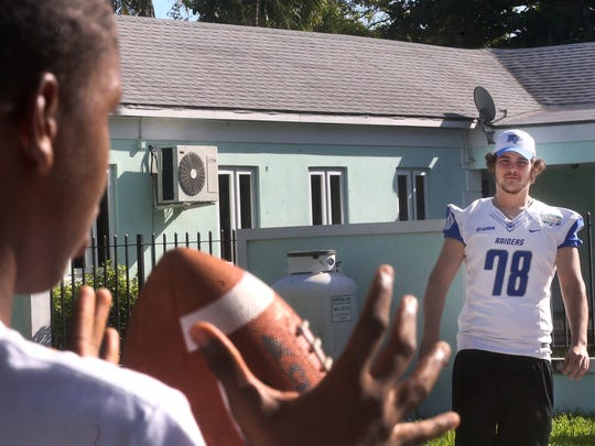 MTSU's Adam Stickle plays a game of catch with a boy from the Ranfurly Homes for Children, during a Popeyes Bahamas Bowl community visit by MTSU and Western Michigan, on Tuesday, Dec. 22, 2015, two days before the teams meet up on the field for the bowl game.