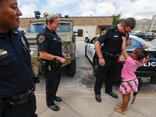 Rosalyn Baldwin, 7, puts a sticker on officer Zach Pugh's uniform during her visit to the Springfield Police Department on Monday, June 5, 2017. Rosalyn is traveling with members of her family to hug police officers in all 50 states. Also pictured are officers Jerome Lockett, left, and Laura Kitta.