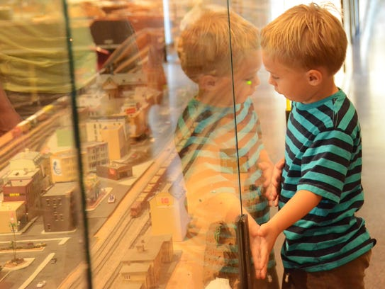 Cash Lesterson, 4, looks through the glass at a model