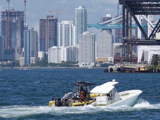 The boat in which Miami Marlins pitcher Jose Fernandez was killed, is towed, Sunday, Sept. 25, 2016, in Miami Beach, Fla. Fernandez and two other people died when their 32-foot vessel slammed into a jetty off Miami Beach, authorities said. (Joe Cavaretta/South Florida Sun-Sentinel via AP)