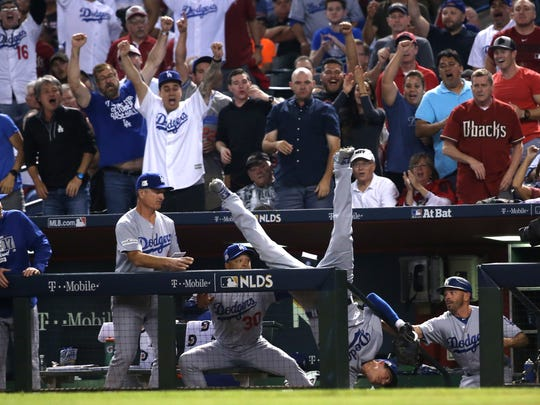 Cody Bellinger falls over the dugout after catching