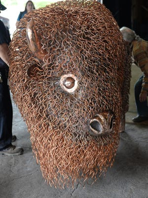 """A life-size copper bison is unloaded June 5 at the Radisson Hotel and Conference Center. Oneida artist Mark Fischer created this sculpture to help promote Native American awareness and named it """"Ancient Dignity."""" The 1,200-pound sculpture will be on public display at the Oneida Nation's Radisson Hotel and Conference Center as part of the Woodland Indian Art Show & Market this weekend."""
