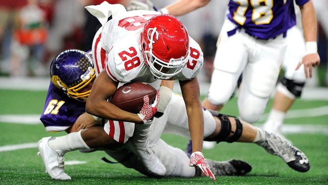 Wylie defensive lineman Kade Parmelly (61) tackles Carthage running back Keaontay Ingram (28) for a loss during the second quarter of Wylie's 31-17 loss in the Class 4A Div. I state championship game on Friday, Dec. 16, 2016, at AT&T Stadium in Arlington.
