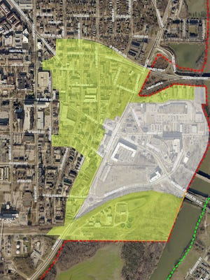 The white area shows the current riverfront development district, while the green is the proposed expansion.