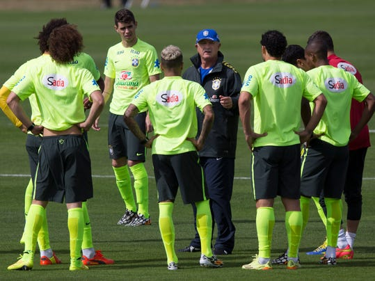 Brazil's coach Luiz Felipe Scolari, wearing a blue hat, gives instructions to his players during a practice session at the Granja Comary training center, in Teresopolis, Brazil, Monday, July 7, 2014. Brazil will face Germany on Tuesday in a World Cup semifinal match without Neymar. (AP Photo/Leo Correa)