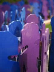 Dozens of purple and blue wooden silhouettes of children,
