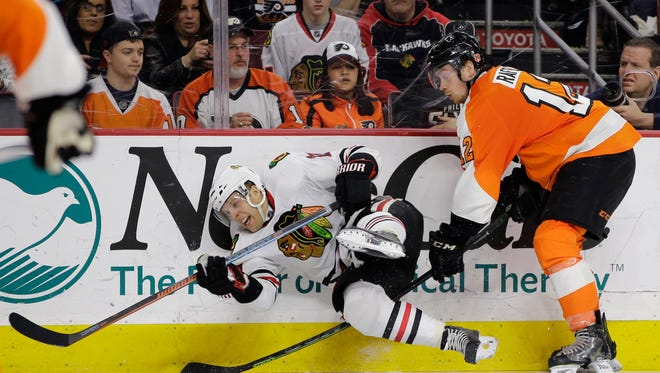 Chicago Blackhawks' Kris Versteeg, center, is sent flying after a check from Philadelphia Flyers' Michael Raffl during the third period Wednesday in Philadelphia. Philadelphia won 4-1.