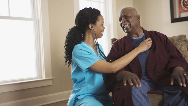 Nurse using stethoscope on patient at home.