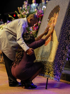 LaTesha Jones is comforted by her father Dedrick Allen as she touches the face of her daughter Cor'Dayja that is imprinted on a blanket during her funeral at the Redemption Point Church on Saturday in Chattanooga. Cor'Dayja's service is the first of six funerals that are being held after the Woodmore Elementary School bus crash.