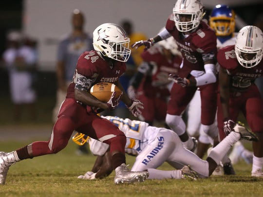 Madison County's Derrick Staten runs with the ball against Rickards during their game at Madison County on Friday.