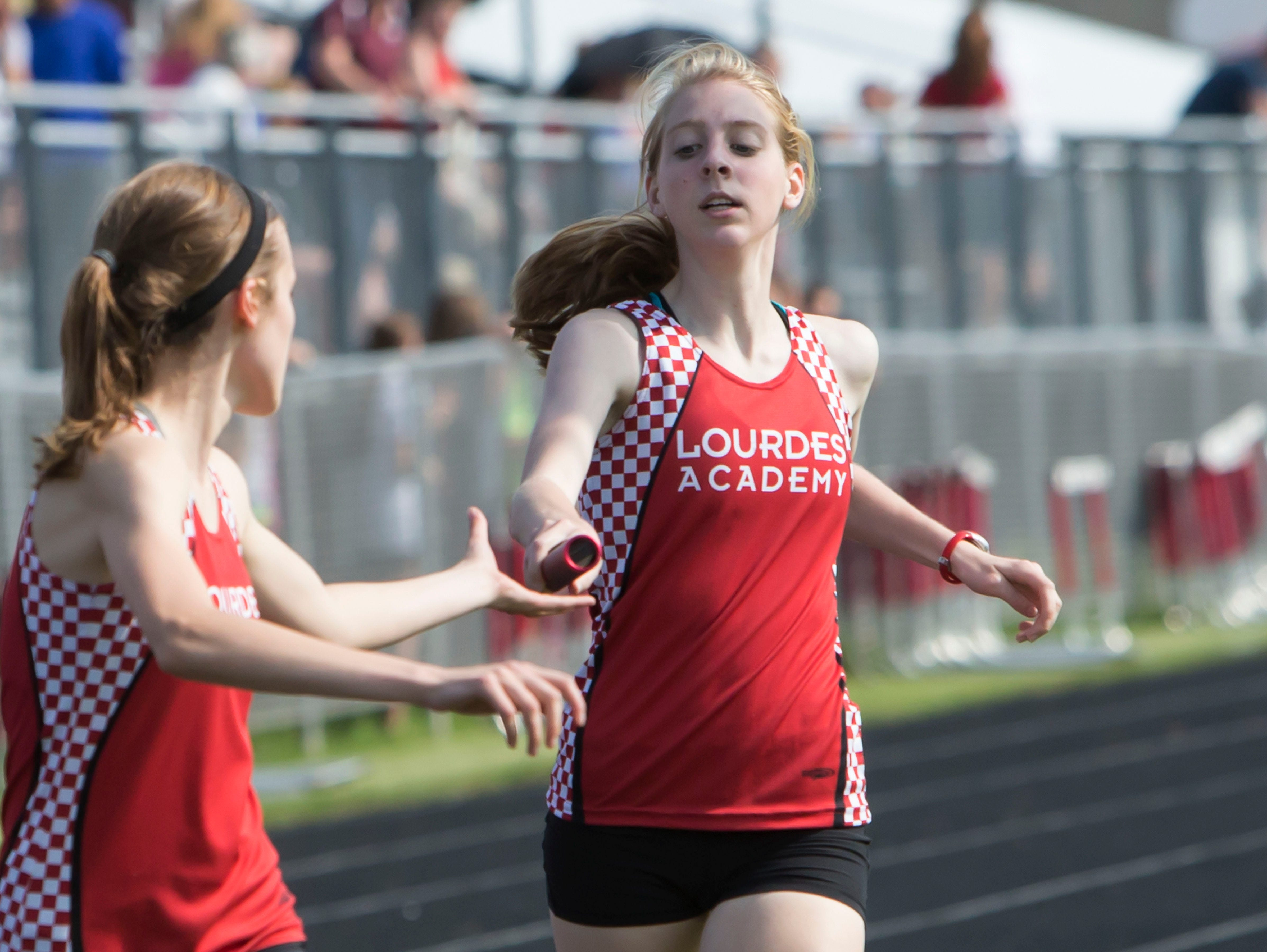 Lourdes Academy's Nora Keller passes the baton to Emily Foley during the 3,200-meter relay at the Princeton sectional on Friday.