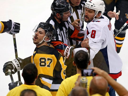 Washington Capitals' Alex Ovechkin (8) grabs Pittsburgh Penguins' Sidney Crosby (87) during the second period in Game 3 of an NHL second-round hockey playoff series in Pittsburgh, Tuesday, May 1, 2018. (AP Photo/Gene J. Puskar)