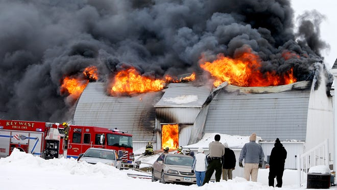 Firefighters from multiple agencies battle a fully engulfed barn fire on the Leonard Schuster farm south of Dubuque, IA, on Dec. 21, 2016.