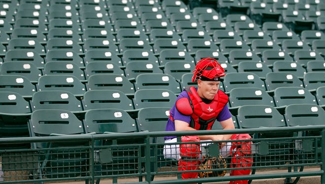 Louisville Bats catcher Chris Berset (14) sits in the stands as he waits for the team's morning workouts to begin at Louisville Slugger Field in Louisville, Kentucky. April 8, 2015