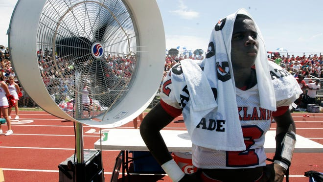 Oakland's Mark Pruitt cools off by a fan on the Oakland sideline Sunday, August 24, 2014 at Blackman.