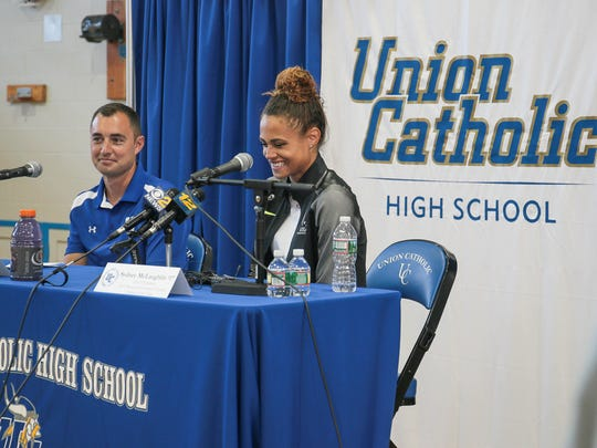 Sydney McLaughlin, right, laughs about a question at