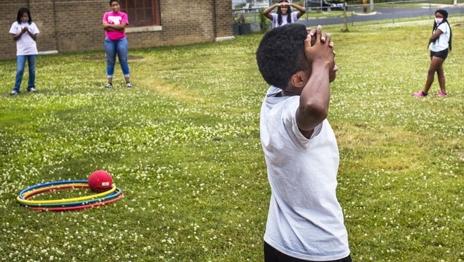 A Peoria Park District Academy summer camper strains to retrieve information from his memory in a challenge from camp counselors Monday, June 22, 2020 at Proctor Center in Peoria. Campers and counselors formed a circle and each in turn performed a short dance move. Others in the circle were then in turn challenged to recall the name of the person and the dance move that preceded them in an effort to work memory and observation skills. The program begins each weekday with breakfast followed by  math and reading classroom work before moving outdoors to expend energy with various physical activities. The session concludes with a sack lunch. The camp is open to children who have completed grades K-7 and live with the Peoria Park District boundaries.