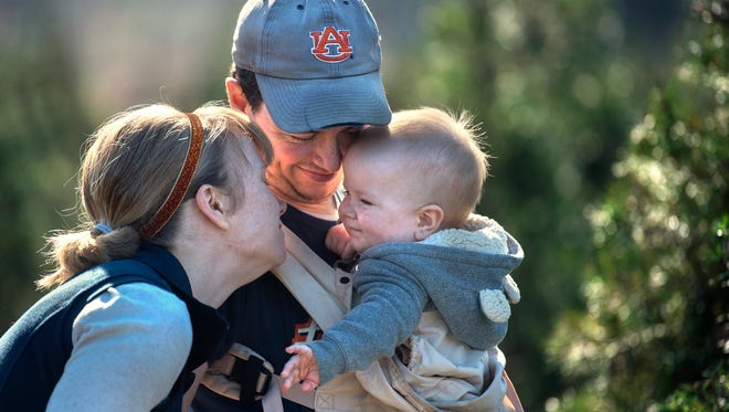 "Between rows of Virginia pine trees, Nicoll and Justin Burleson, of Three Way, share a moment with their 9-month-old son, Branch, while Christmas-trees shopping Saturday, Dec. 2, 2017, at the Ward Grove Christmas Tree Farm in Beech Bluff. Nicoll and Justin have been coming to Ward Grove with their three sons, Bridger, Beacon and Branch, since they moved to Three Way over two years ago. ""We love doing this together each year,"" Nicoll said. ""Just to get fresh air and drive in the car and listen to Christmas music. We may not have the one-time cost of an artificial tree to put up for 10 years, but it's worth it for the experience to us."" The Burlesons chose to name this year's Christmas tree ""Penguin Bear Burleson,"" after their sons' favorite winter animals."