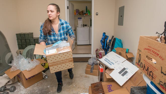 Michelle Lewis goes through boxes at her new house in Pensacola on Tuesday, January 9, 2018.