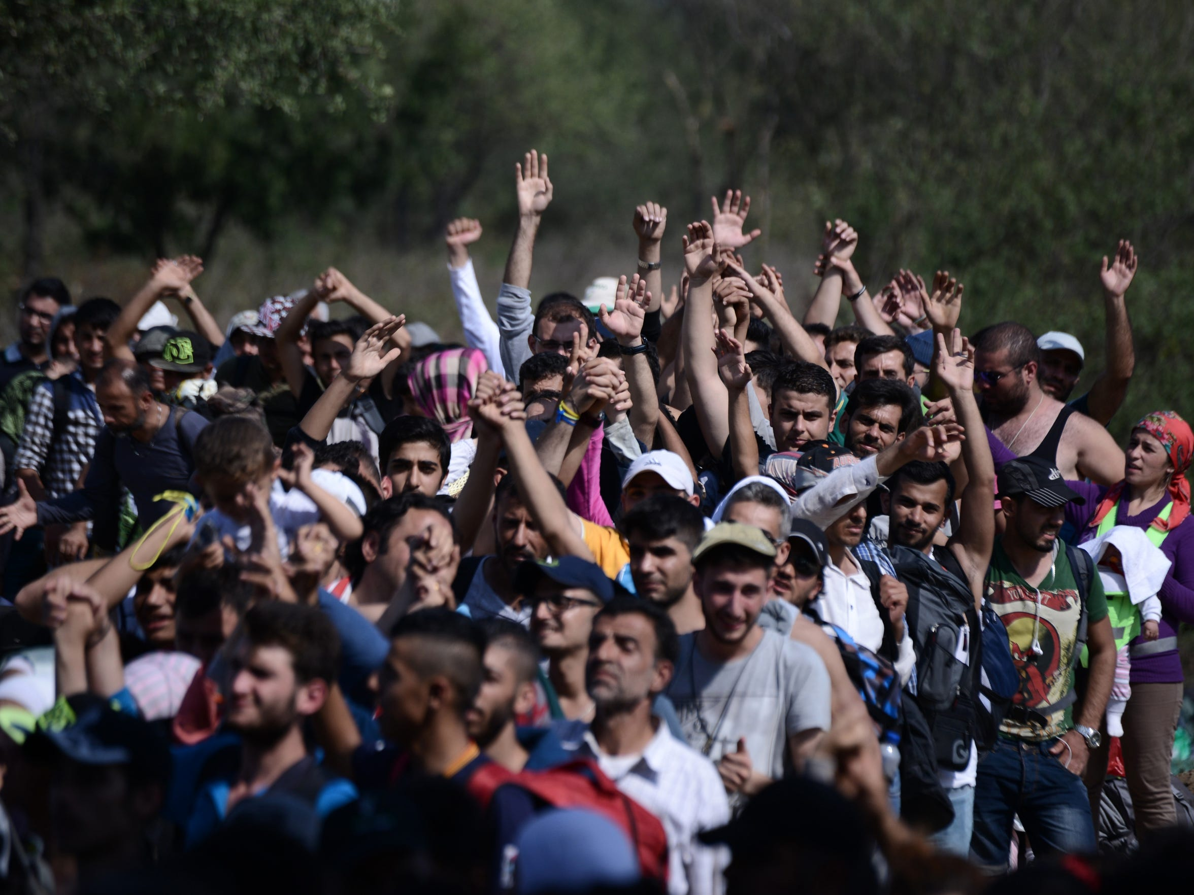 Refugees and migrants raise their hands in order to be allowed by the Macedonian police to cross the border from the northern Greek village of Idomeni to southern Macedonia, on Sept. 20, 2015.