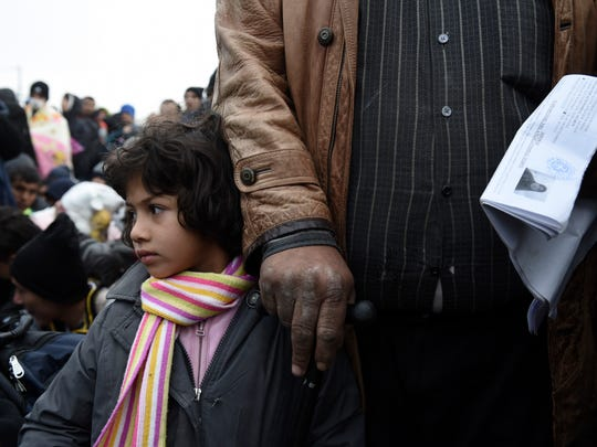 A Syrian girl with her father wait to be allowed by