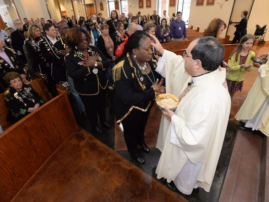 FILE: Bishop Michael Duca performs communion as he presides over a 12th Night Mardi Gras mass at St. Pius Catholic Church in Shreveport.