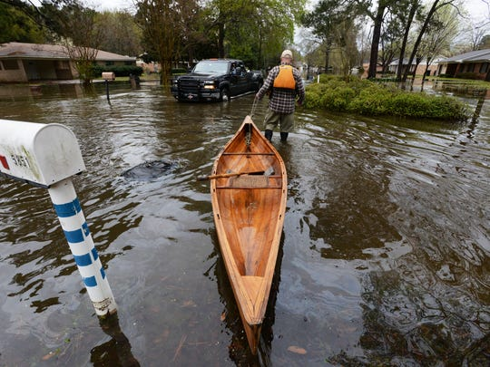 Richard Maxwell gets to his house with the help of a canoe on Dianne Street just south of Caddo Lake in Shreveport, Louisiana.