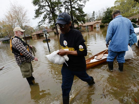 Sylvester LaCour grabs sandbags for his house with the help of friends and neighbors Friday afternoon on Dianne Street just south of Caddo Lake in Shreveport, Louisiana.