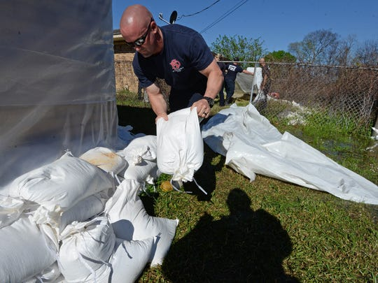 Matt Head of the Shreveport Fire Department helps his fellow members from Central Station and the fire academy lay sandbags on Oregon Avenue Shreveport. Now that the rains have let up, water from Twelve Mile Bayou has begun to creep into surrounding neighborhoods. .