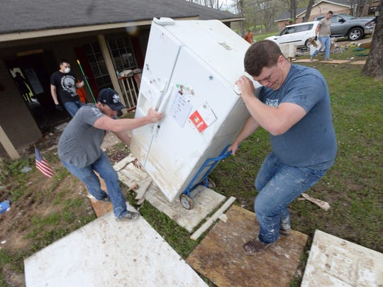 Volunteers remove the refigerator for a flood damaged home in the Tall Timbers subdivision.