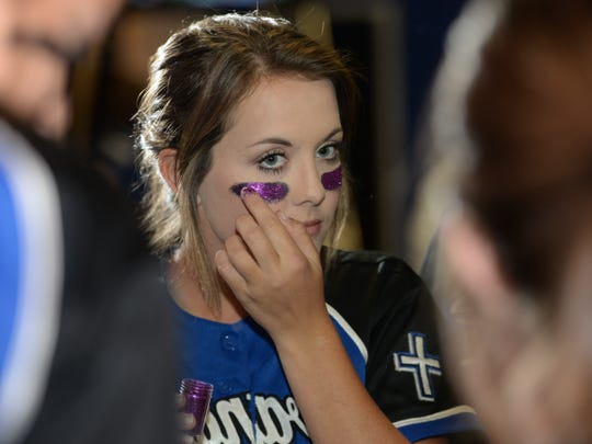 Claire McMillan puts sparkles on her eye black before