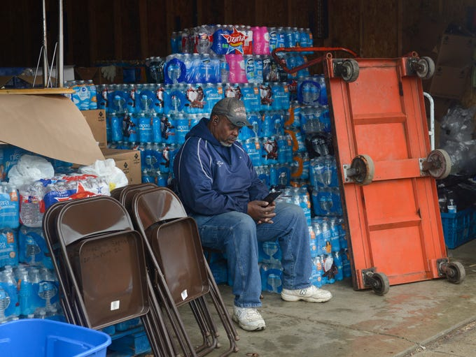 Eric Lawson takes a break from  loading water into