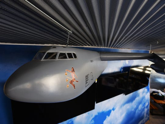 A model of a B-52 fuselage juts out of wall at the