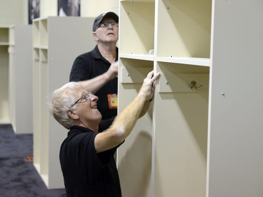 Harry Baenen, back, and Jeff Judkins, of the Green Bay Packers facilities team prepare a temporary locker room in the Lambeau Field gym. Aug. 26, 2016.