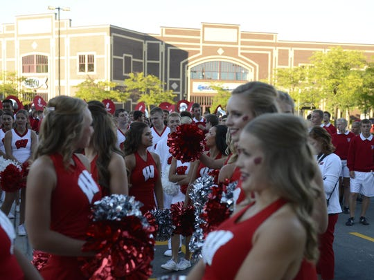 University of Wisconsin Marching Band Spirit Squad members gather in downtown Green Bay on Friday before marching to the Bucky Block Party at Titletown Brewing Co.