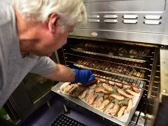Rich Jarocki, a volunteer at Meals with a Mission, checks on chicken cooking at the Garfield facility.